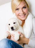 Close up of woman with white puppy on her knees stock photography