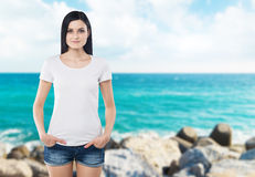 Close-up of a woman in a white t-shirt. Hands in the pockets of denim shorts. Royalty Free Stock Images