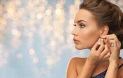 Close up of woman woman fastening diamond earring Stock Image