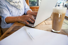 Close up of woman working on laptop computer by cold coffee at table Stock Photo