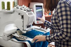 Close-up of woman working on modern computerized embroidery machine creating green floral pattern. Close-up of woman working on modern computerized specially royalty free stock photos