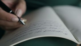 Close-up of a woman writing a hand on an empty notebook with a pen. Slow motion stock video
