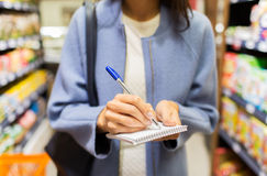 Close up of woman writing to notepad in market Stock Photo