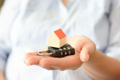 Close-up of woman's hands holding a small model house on top of a cipher lock Stock Image
