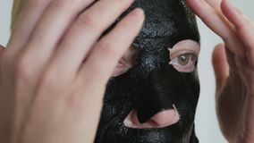 Woman, 40 years old applying a rejuvenating cosmetic black tissue mask to her face. Close-up of a woman, 40 years old applying a rejuvenating cosmetic black stock video footage