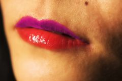 A close up of a womans bi-colored lips. A close up of a woman wearing lipstick dual colors, pink and purple stock image