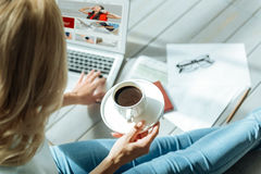 Close up of womans hands holding a cup of coffee and laptop Royalty Free Stock Photography