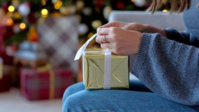 Close up - Womans hands prepares a new year surprise, tying a bow on a gold box with a gift. Xmas 2019. Close up - Womans hands prepares a new year surprise stock video footage