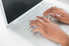 Close up on womans hands typing on her laptop. In bright fitness studio Royalty Free Stock Photography