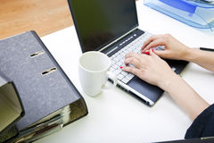 Close up of womans hands typing on laptop with folders and mug Stock Photo