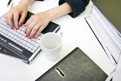 Close up of womans hands typing on laptop with folders and mug Stock Images