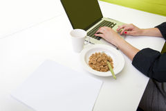 Close up of womans hands typing on laptop with mug in foreground Stock Images