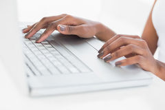 Close up on womans hands using her laptop. In bright fitness studio Stock Image