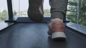 Close up womans legs in pink sneakers on a. Treadmill in the gym. Slider camera movement forward. Beautiful legs. The royalty free stock photography