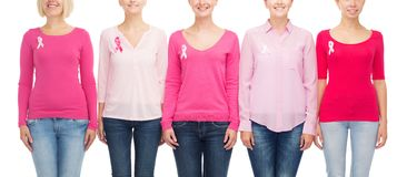 Close up of women with cancer awareness ribbons. Healthcare, people and medicine concept - close up of smiling women in blank shirts with pink breast cancer royalty free stock images