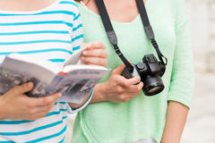 Close up of women with city guide and camera. Tourism, travel, leisure and friendship concept - close up of women with city guide and camera outdoors Stock Photos