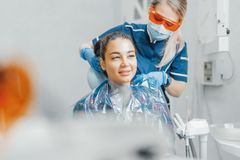 Close up of woman dentist putting on plastic apron on smiling woman client. royalty free stock image