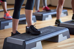 Close up of women exercising with steppers in gym Stock Photo
