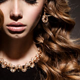 Close-up women face with long curly hair and gold jewelry Stock Photography