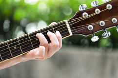 A close up of women fingers playing guitar Stock Photo