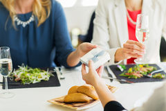 Close up of women giving present at restaurant Stock Photography