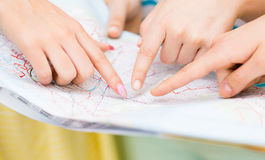 Close up of women hands pointing finger to map. Tourism, travel, location and destination concept - close up of women hands pointing finger to map Royalty Free Stock Image