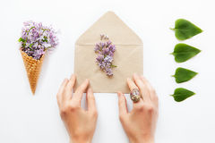 Close up women hands touching opened craft paper envelope filled with purple lilac flowers surrounded by a waffle corn with a bouq. Uet of lilac and a row of Stock Image