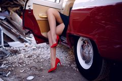 Close up of a women legs in red shoes heels sitting inside on vintage red car on iron dump background. Horizontal view. stock image
