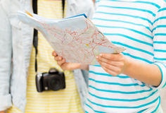 Close up of women with map and camera outdoors. Tourism, travel, leisure, holidays and friendship concept - close up of women with map and camera outdoors Stock Photo