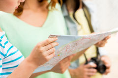 Close up of women with map and camera outdoors. Tourism, travel, leisure, holidays and friendship concept - close up of women with map and camera outdoors Stock Image