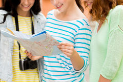 Close up of women with map and camera outdoors. Tourism, travel, leisure, holidays and friendship concept - close up of smiling teenage girls with map and camera Stock Photos
