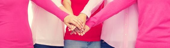 Close up of women in pink shirts with hands on top Royalty Free Stock Images