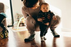 Woman holding her baby squatting on floor stock image