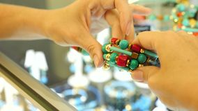 Close-up. Women`s hands hold a bracelet of turquoise and coral over the counter in the jewelry store. 4k, slow motion. Close-up. Women`s hands hold a bracelet stock footage