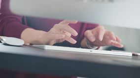 Close-up: women`s hands quickly typing on the keyboard of the computer. Text or message typing. Woman is working in the office and typing text, clicking on the stock video footage