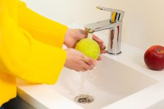 Close up of women`s hands washing green apple in sink.  royalty free stock photo