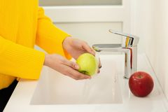 Close up of women`s hands washing green apple in sink.  stock photos