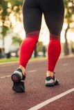 Close up of women`s shoes walking outdoors in running shoes from behind. Black and pink sportswear and sneakers royalty free stock photo