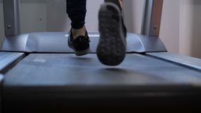 Close-up. Women`s sneakers run on a treadmill. 4K Slow Mo stock video