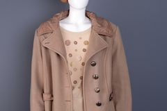 Close up women stylish overcoat on mannequin. Female beige blouse and cashmere top coat Stock Image