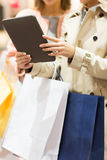 Close up of women with tablet pc and shopping bags Stock Photo