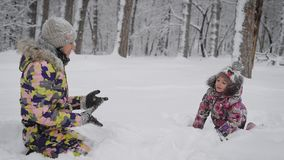 Close up of wonderful family playing together in winter forest. Young woman is sitting in the snow waiting for her stock footage