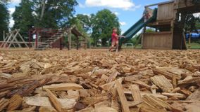Close up of wood chippings and children playing on a playground. Bark child boy girl sitting on slide in background focus ground relaxing jungle gym sliding royalty free stock image