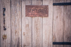 Close up of wood door with guest only sign Stock Image