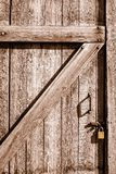 Close-up of wood door to an old house bolted shut with flat gold. This door is bolted from the outside and locked with a smooth gold padlock. It is an older stock photos
