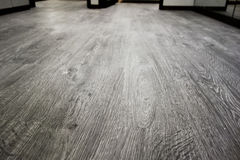 Close-up of a wood laminate floor in a new house. Empty room interior, gray wood laminate floor and white mortar wall Stock Images