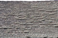 Close up on a wood shake shingle roof in poor repair. Wood shingle roof in poor repair. Wood shingles are thin, tapered pieces of wood primarily used to cover Stock Photo