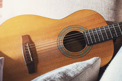 Close-up wooden acoustic guitar on fabric sofa with pillows, vintage tone soft focus Stock Photo