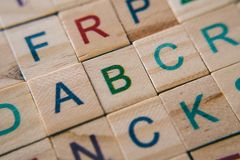 Close up of wooden alphabet tiles focus on letter A B and C royalty free stock image