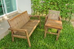 Wooden bench and chair on green lawn for sitting. Close up wooden bench and chair on green lawn for sitting royalty free stock photos